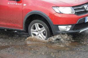 guidare Le 10 regole per guidare quando piove pioggia bagnato buca guida 5 300x199